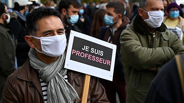 """Paris'te saldırıya tepki gösteren bir vatandaş, """"Ben öğretmenim"""" yazan bir pankart taşıyor."""