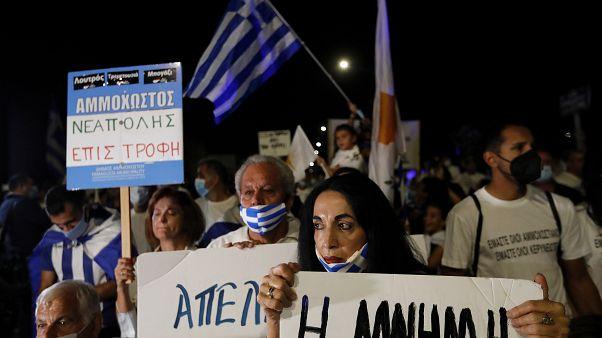 """Eine griechische Zyprerin hält ein Plakat mit der Aufschrift """"Erinnerung"""" hoch"""