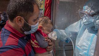 عامل صحي في كشمير يأخذ عينة مسحة أنف لطفل لاختبار كوفيد-19