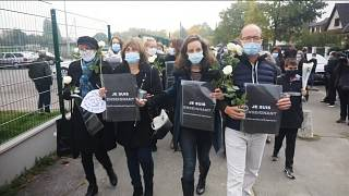 Various of mourners walking with flowers and placards reading (French) 'I am a teacher'