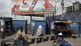A billboard promoting presidential candidate Carlos Mesa of the Citizen Community political party towers over a trio of women in Rio Seco, Bolivia, Saturday, Oct. 17, 2020