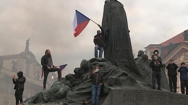 Men waving Czech flags from monument