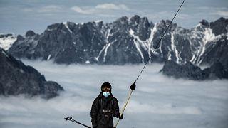 Un skieur porte un masque sur une remontée mécanique dans la station des 2 Alpes, le 17 octobre 2020