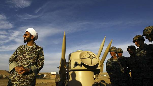 In this Nov. 13, 2012 file photo, an Iranian clergyman stands next to missiles and army troops, during a manoeuvre, in an undisclosed location in Iran.