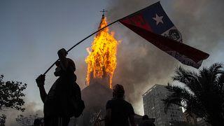 Un manifestante enarbola una bandera de Chile frente a la cúpula de la Asunción en llamas