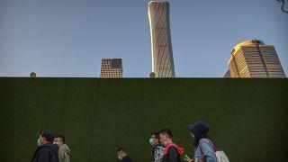 Des personnes portant des masques de protection contre le Covid-19 marchent dans une rue du quartier central des affaires de Pékin, vendredi 16 octobre 2020