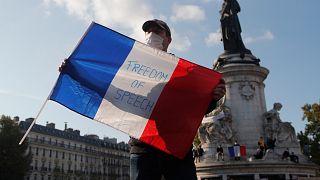 """Мужчина с французским флагом, на котором написано """"Свобода слова""""."""