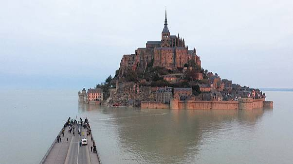 Wide shot Mont-Saint-Michel surrounded by the sea during high tide (drone images)