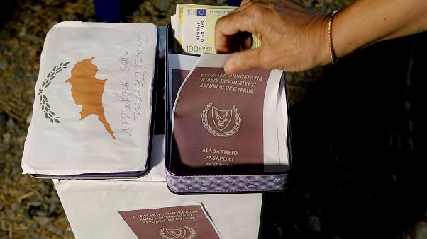 A demonstrator takes a mock copy of Cyprus passport during a demonstration against corruption in the capital Nicosia, Cyprus, Wednesday, Oct. 14 2020