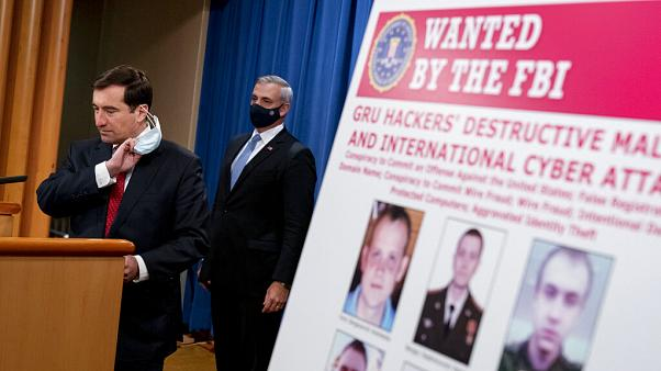 A poster showing six wanted Russian military intelligence officers is displayed as Assistant Attorney General for the National Security Division John Demers, speaks.