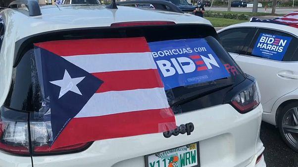 """Un vehículo con una bandera de Puerto Rico y el cartel """"Boricuas con Biden"""""""