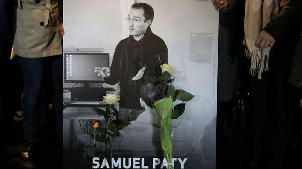 مشاركان في مسيرة في باريس يمسكان بصورة المدرس الفرنسي صاموئيل باتي الذي قطع رأسه الأسبوع الماضي. 2020/0/10/20