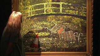 امراة تتأمل في لوحة زيتية لبانسكي في مزاد في لندن. 2020/10/20