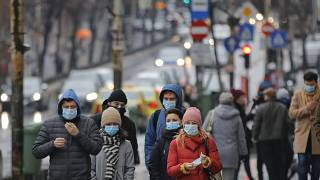 People walk wearing masks during an anti-pollution protest outside the city hall in Bucharest, Romania, Wednesday, Dec. 12, 2018.