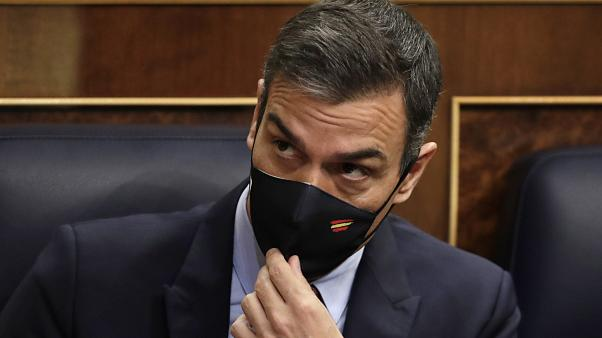 Spain's Prime Minister Pedro Sanchez adjusts his face mask at a parliamentary session ahead of a no-confidence vote. Madrid, Spain. October 21, 2020.