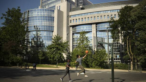Youngsters play basketball in front of the European Parliament building in Brussels, Wednesday, May 15, 2019.