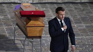 French President Emmanuel Macron leaves after paying his respects by the coffin of slain teacher Samuel Paty in the courtyard of the Sorbonne university, Paris.