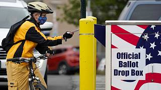 Il ciclista Mickey McDiarmid vota inserendo la scheda in un'urna elettorale per il voto postale lo scorso lunedì 19 ottobre 2020 a Bellingham, Washington