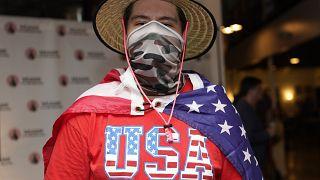 """Un joven latino asiste envuelto en una bandera estadounidense a uno de los debates de """"Latinos for Trump"""""""