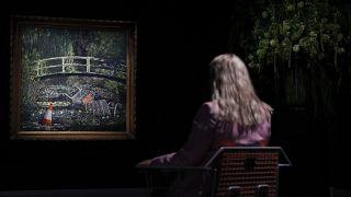 Eine Londoner Sotheby` s `Mitarbeiterin scheint im jetzt versteigerten Banky-Werk förmlich zu versinken
