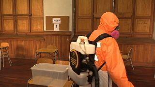 Un trabajador desinfectando un centro de votación en Santiago