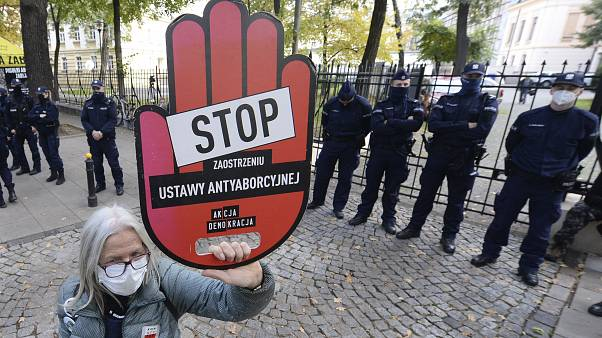 "A protester holds a sign reading ""stop tightening the law"" at a pro-choice protest in front of Poland's constitutional court. Warsaw, Poland. Oct. 22, 2020."