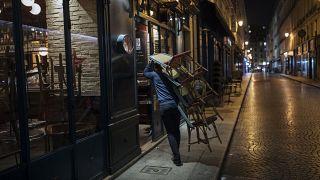 A waiter closes a bar terrace in Paris, Saturday, Oct. 17, 2020.