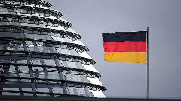 A flag of Germany waves next to the dome of the Reichstag building where the German federal parliament Bundestag meets.