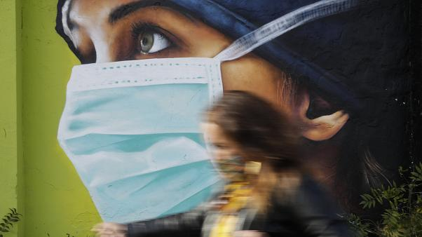A woman walks in from of a mural painting of a nurse, in Milan, Italy, Wednesday, Oct. 14, 2020.