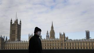A man wears a face mask as he passes Britain's Parliament in London, Friday, Oct. 16, 2020.