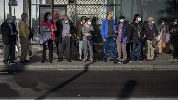 People wearing masks wait for a bus in Barcelona. Spain has reported over a million cases of COVID-19