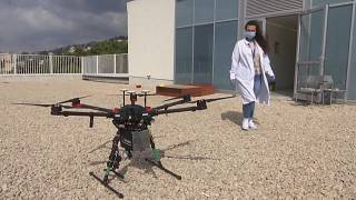 Woman from medical staff taking box carried by drone