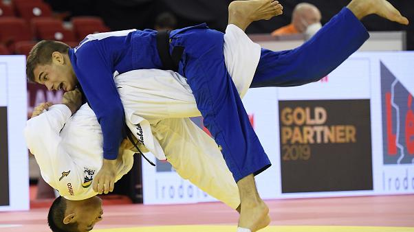 Eric Takabatake, bottom, of Brazil and Marton Andrasi of Hungary fight in the men's -66 kg category of the Judo Grand Slam Budapest