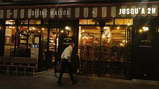 A waiters cleans the terrace of a restaurant before the nightly curfew due to the restrictions against the spread of the Coronavirus disease, in Paris