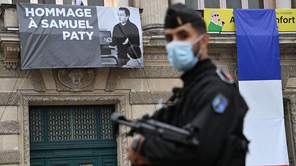 رجل أمن فرنسي وخلفه صورة لصامويل باتي
