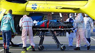 طاقم طبي يحمل على نقالة، مريض مصاب بفيروس كوفيد -19 على طائرة هليكوبتر من مستشفى فليفو في ألمير، إلى مونستر، ألمانيا، 23 أكتوبر 2020