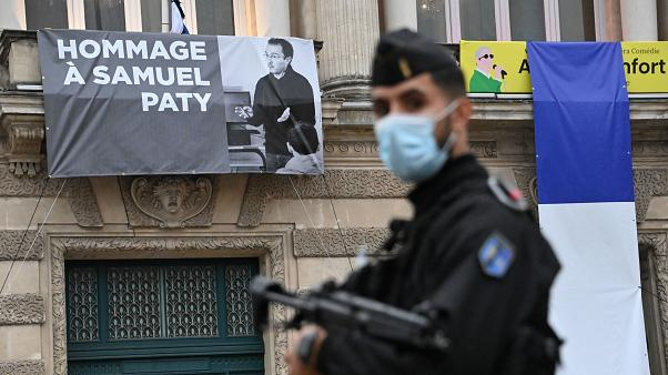 A police officer next to a portrait of murdered French teacher Samuel Paty