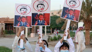 أطفال كويتيون يرفعون لافتات تعبر عن غضبهم من الرئيس الفرنسي إيمانويل ماكرون