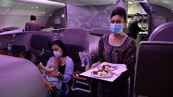 مضيفة الخطوط الجوية السنغافورية تبتسم أثناء تقديم الطعام على متن طائرة إيرباص A380 التابعة للخطوط الجوية السنغافورية، مطار شانغي الدولي في سنغافورة 24 أكتوبر 2020