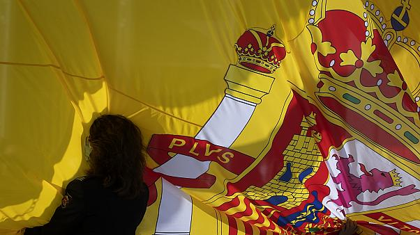 A woman holds a Spanish flag during a memorial for coronavirus victims in Madrid, Spain, Friday, October 23, 2020.