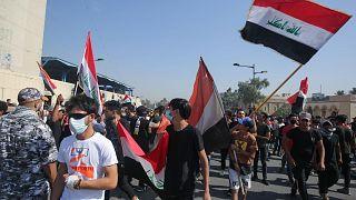 متظاهرون عراقيون يلوحون بالأعلام أثناء تجمعهم في ساحة التحرير وسط العاصمة بغداد، 25 أكتوبر / تشرين الأول 2020