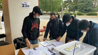 Un grupo de jóvenes revisa las listas en un colegio electoral a cielo abierto