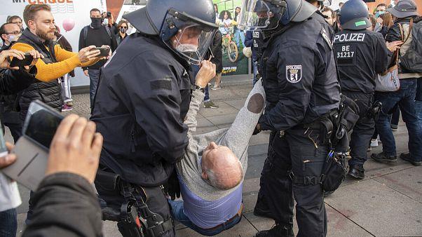 Polizisten tragen Teilnehmer einer Anti-Corona-Demonstration auf dem Alexanderplatz weg, 25.10.2020