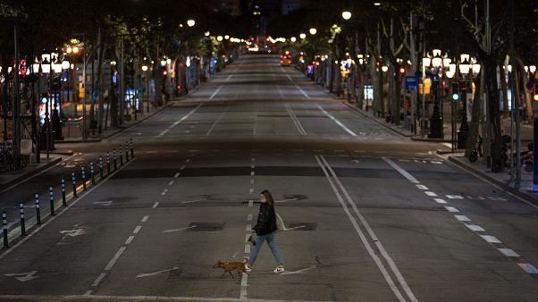 Una mujer cruza una calle vacía de Barcelona