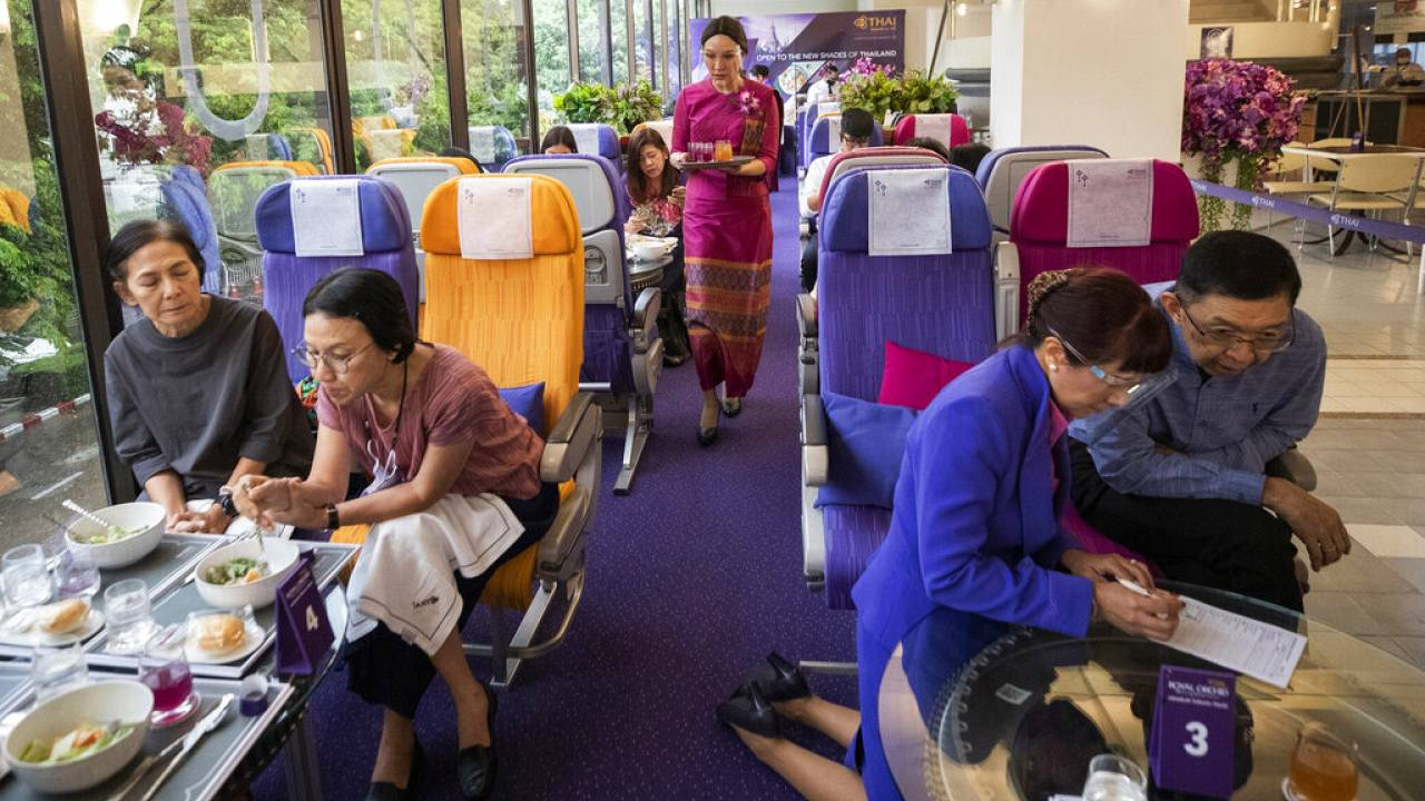 A flight attendant serves welcome drinks in a flight-themed restaurant at the Thai Airways head office in Bangkok