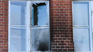 The damaged windows of the Robert Koch Institute in Berlin, Germany, Sunday, Oct.25, 2020. According to police, bottles and incendiary devices were thrown at the building.