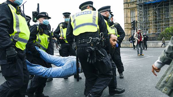 Londra, 24 ottobre: la polizia trascina via di peso un manifestante nella protesta contro le restrizioni