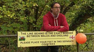 رجل يقف بين حدود الويلز وإنجلترا في بلدة نايتون