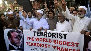 Pakistan traders hold a banner with a defaced picture of French President Emmanuel Macron during a protest against the publishing of caricatures of the Prophet Muhammad.