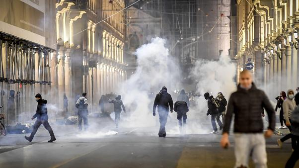 Smoke billows as clashes broke out during a protest against the government restriction measures to curb the spread of COVID-19 in Turin, Italy, Monday, Oct. 26, 2020.